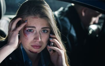 Injured passenger calling for a help after a road accident