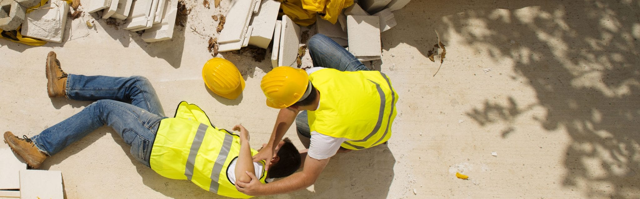 A man taking care of another co-worker's injury at construction site